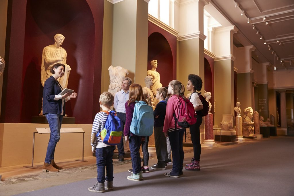 teacher touring her students in a museum