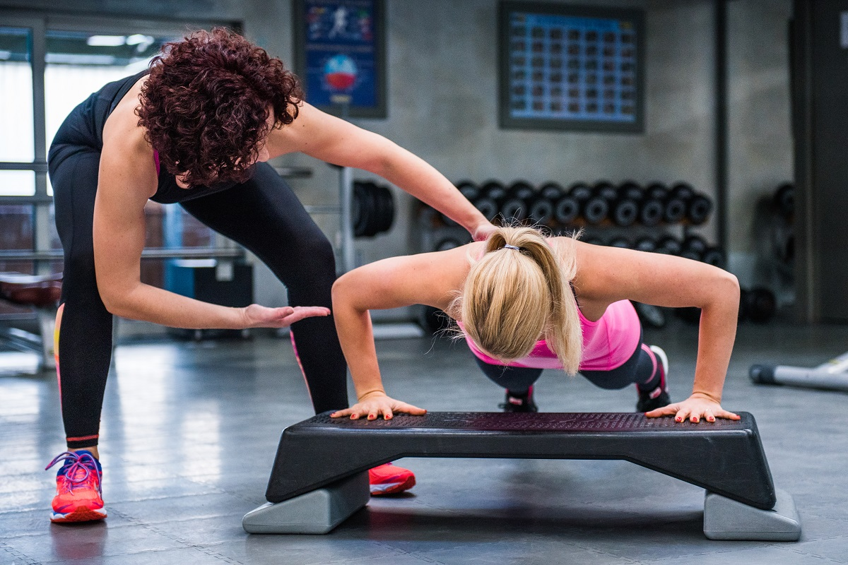 fitness trainer and woman at the gym