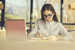 woman writing notes in front of laptop