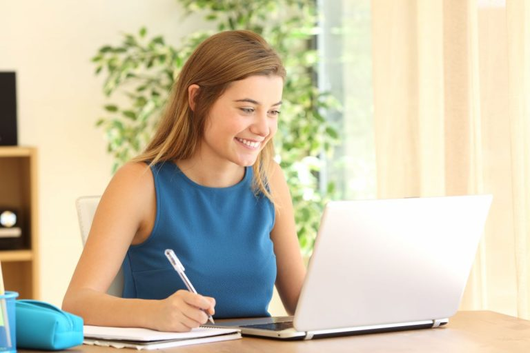 woman taking notes in front of laptop